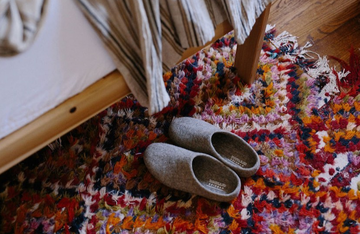 Photo of wool slippers by Kyrgies on EarthHero on top of a colorful rug next to a feat with a blanket on it.