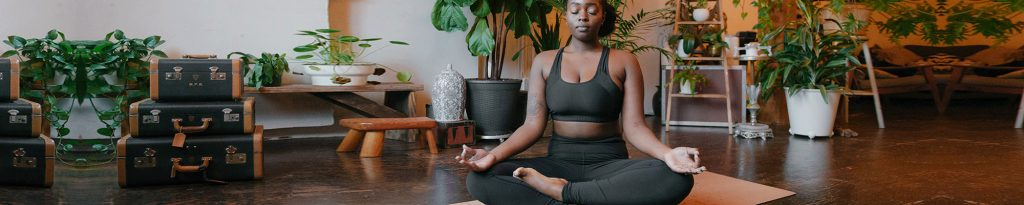 Person sitting cross legged and meditating in a room with plants