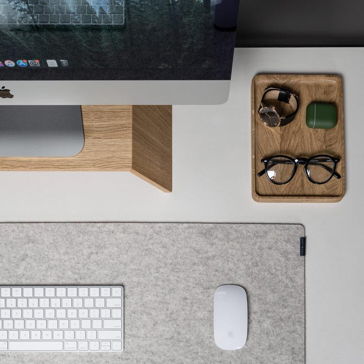 Photo of a workspace with a desktop, keyboard and mouse, and a basket with glasses, watch and an air pods case
