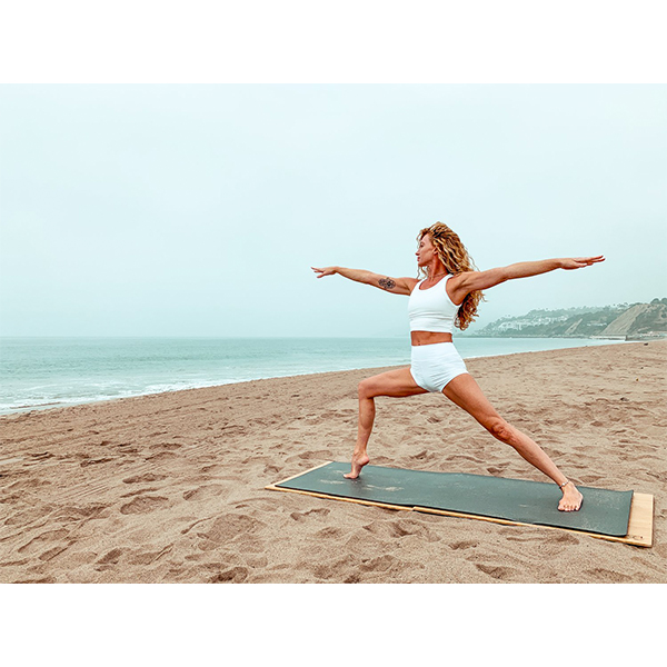 A person doing a Warrior I yoga pose on a yoga mat at the beach and using The Root Board from EarthHero