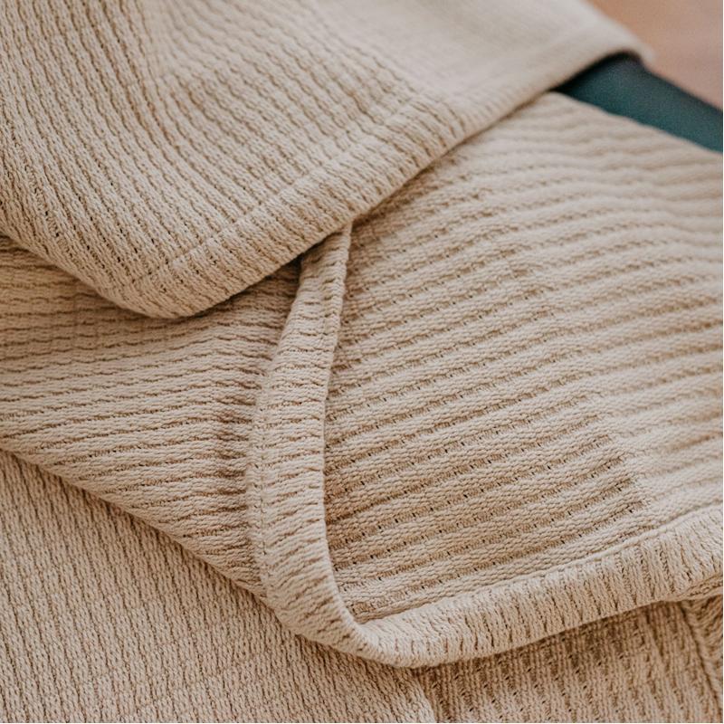 A beige blanket from Grund called Sea Throw Blanket on EarthHero