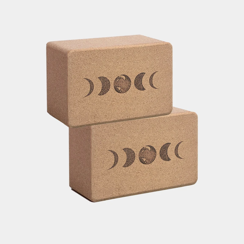 Stacked cork yoga blocks with the phases of the moon on them from the brand Scoria on EarthHero.