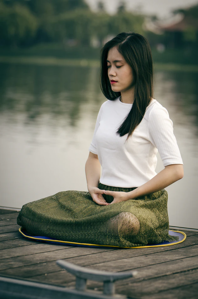 Person meditating by a lake with eyes closed and wearing a white shirt and green bottoms.
